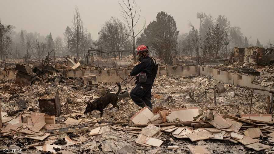 يواصل رجال الإنقاذ أعمالهم وسط الركام الذي خلفه حرائق الغابات.