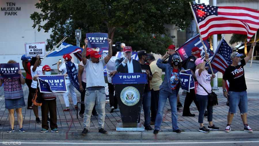 """ومؤيدو الرئيس يحاولون إفساد تجمع لمنافسيهم مستعينين بـ""""ترامب مزيف""""."""