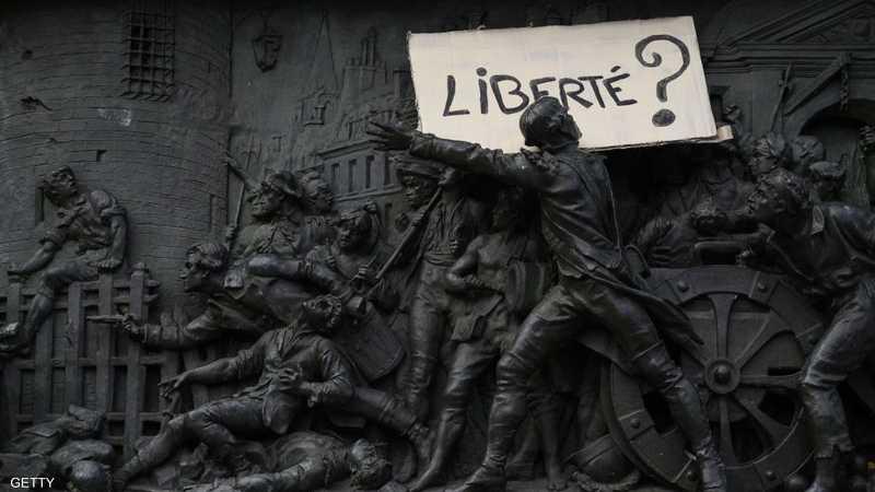 """لافتة عن """"الحرية"""" فوق تمثال أثناء الاحتجاج على القانون المثير للجدل"""