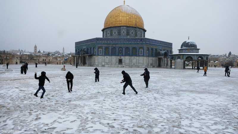 يلعب الناس بأكوام الثلج بجانب قبة الصخرة في القدس