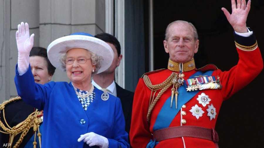 ملكة بريطانيا والأمير فيليب يلوحان من شرفة قصر باكنغهام