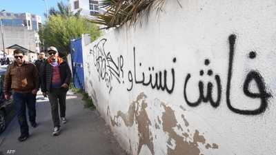 تونسيون يمرون جانب حائط وعبارة تندد بالميزانية في تونس