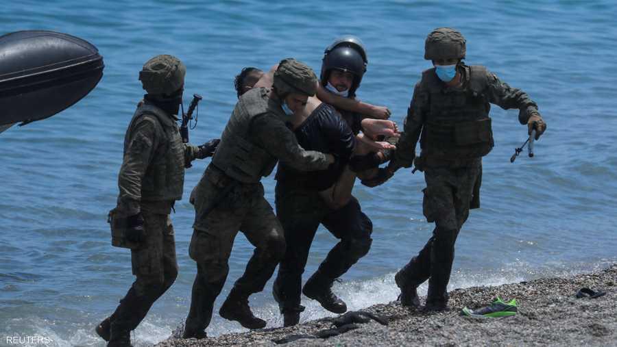 يحملون مهاجرا من البحر