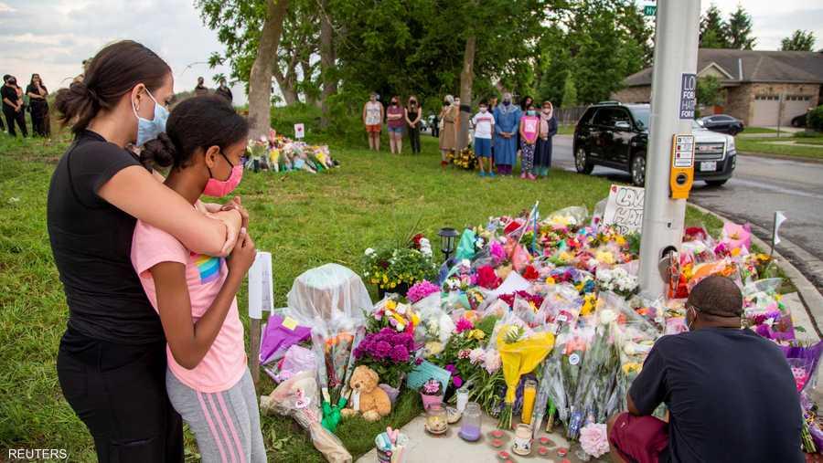 سكان مدينة لندن أمام زهور وضعت في مكان الهجوم