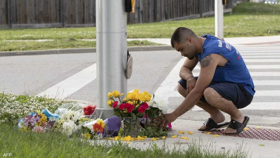 أحد سكان المدينة يضع الأزهار في موقع الهجوم